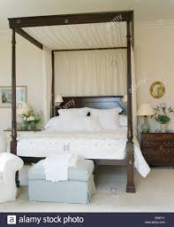 Cream drapes on dark wood four poster bed with white linen in ...