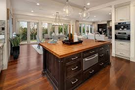kitchen island with wood countertop dark cabinet and hickory floors