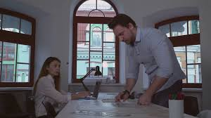 the creative office. Two Architect Working In The Creative Office. Woman Typing On Laptop, Man Reading Building Plan Writing Notes Notebook. Team Looking At Camera With Office O