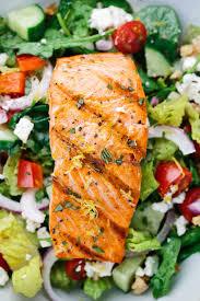 grilled salmon fillet on top of a greek salad