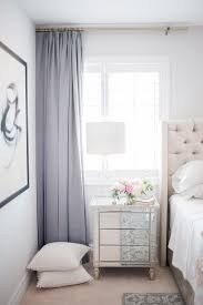 feminine bedroom with violet curtains a creme upholstered headboard and a mirrored vanity