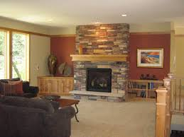interior brown wooden mantel shelf of grey stone fireplace with black metal fire box near