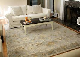 what size area rug for living room combined with clean white rabric upholstery sofa and white wooden table in blask surface facing fire place