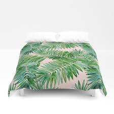 green palm leaves on a light pink