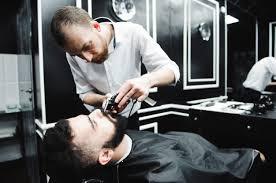 Мастер стрижет волосы и бороду мужчин в парикмахерской ...