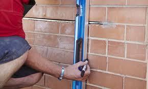 man installing a lintel in a brick wall