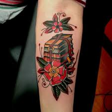 red flowers and book tattoo on arm