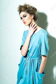 pretty fashionable woman with bright makeup and chignon in light blue dress standing on white background