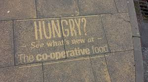 reverse graffiti pavement advertising blast away clean ads co op food store clean adverts in manchester