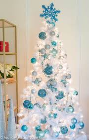 I love the idea of using a white Christmas tree and then pops of color  through ornaments. The blue, silver and white decor look fabulous when the  tree is ...