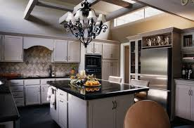 black iron with white shade chandelier over kitchen island full size