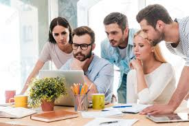 successful business team at work group of confident business stock photo successful business team at work group of confident business people in smart casual wear looking at the laptop together