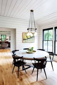 modern farmhouse style dining room design featuring white shiplap walls and ceiling a round table black painted wood chairs and a vine industrial