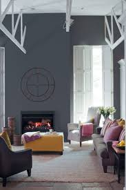 using a dark charcoal paint on the fireplace wall makes it a focal point and creates a good contrast to the warm blaze of these gas flames