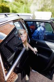 looking through open door of car with brother in background stock photo