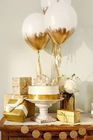 white and gold balloons over table of cake and gifts as an idea for bridal shower
