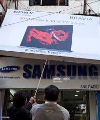 sony tv outlet. workers lift a sony corp. bravia advertisement outside an electronics outlet in new delhi, tv