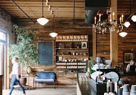 Warm, distressed wood surrounds this rustic coffee shop. Modern pendant  lightings and dainty chandelier