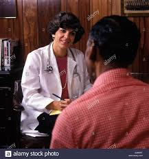 s female doctor interviewing african american male patient 1980s female doctor interviewing african american male patient