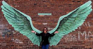 a member of the public poses with an interactive artwork by former geologist turned  on angel wings wall art liverpool with liverpudlians are loving their city s new liver birds street mural i