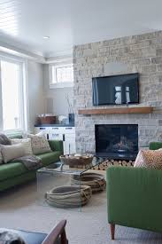 magnificent wood fireplace mantels in family room transitional with green sofa next to wall mount tv alongside wood ceiling and revere pewter