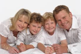 background casual family portrait with mum dad and 2 young sons wearing casual white tops shot on