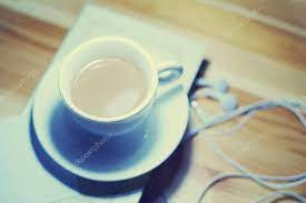cup of coffee book and earphones on