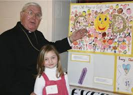 respect life poster and essay contest winners the monitor  sharing a smile bishop john m smith admires the artwork of devon pasieka