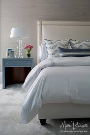chic bedroom boasts a wall clad in gray grasscloth wallpaper lined with an ivory headboard with brass nailhead trim on bed dressed in white and blue bedding