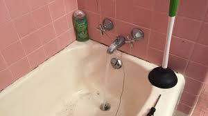 How to Unclog a Bathtub Drain with Standing Water Using a Coat ...