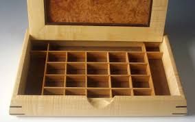 mens jewelry box made of exotic woods that is shown open to reveal cubed compartments for
