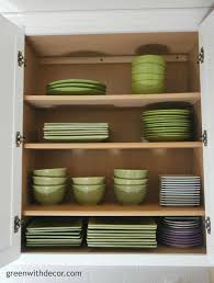 add extra storage in the kitchen cabinets with this easy trick green with decor