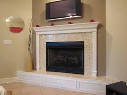 appealing home interior fireplace decor with glitter glass mosaic tiles and raised hearth plus cool white wooden shelving below wall mount tv as well as