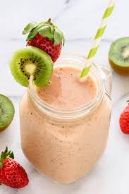mason jar gl with a strawberry kiwi smoothie rimmed with fresh kiwi slice and a strawberry