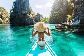 back view of the young woman in straw hat relaxing on the boat and looking forward palawan philippines