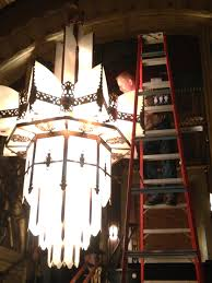 a ladder is used to reach the bulbs in the top half of the chandelier
