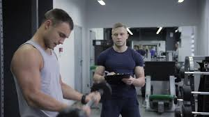 gym instructor personal trainer counts number of exercises man has with a barbell