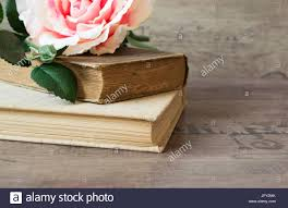 old books and flower rose on a wooden background romantic fl frame background picture of a flowers lying on an antique book flowers on vine