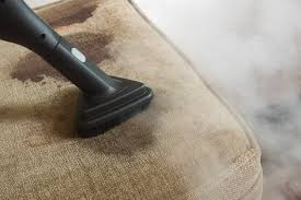 carpet upholstery cleaner. a beige cushion with stains on it and the black extension of carpet cleaner working upholstery l