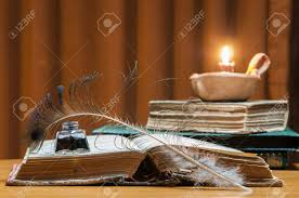 quill pen inkwell and an open old book by candle light stock photo 80998490