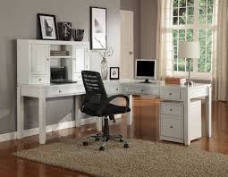lovely home office setup click. Lovely Custom Home Office Designs With White Wooden L Shaped Table And Shelf Under Computer Tube Lamp Also Black Wheeled Chair On Cream Setup Click E