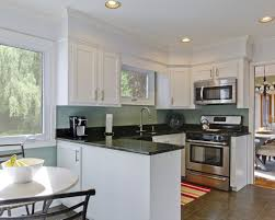 small u shaped kitchen with island marble counter top small white plant pots white countertop glass