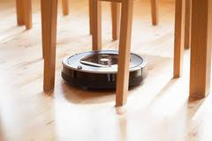 Robotic Vacuum Cleaner On Laminate Wood Floor Smart Cleaning Tec Royalty  Free Stock Photo
