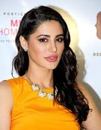 nargis fakhriin dkny yellow dress which showed white and gold chunky necklace curly hairstyles with