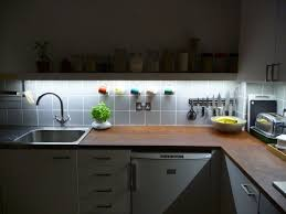 lighting charming led rope lights under kitchen cabinets with white kitchen cabinets and brown concrete backsplash lighting