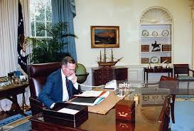 george bush oval office. bush sitting at his wh oval office desk chatting on phone pausing george