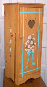 tall cabinet, handpainted with daisies and aqua trim. Has an attached  wooden