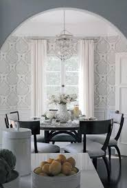 clically beautiful dining room features an dark wood round dining table surrounded by black klismos dining chairs ed with light gray cushions