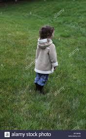 tall green grass field. A Small Girl Standing In Field Of Tall Green Grass And Looking Into The Distance