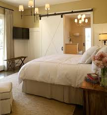 beautiful bedroom with sliding barn door yellow walls paint color tv taupe pinch pleat curtains seagrass rug bryant chandelier in bronze